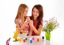 Två flickor - systrar som har roliga målningpåskägg Royaltyfri Bild