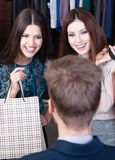 Två flickor talar till affärsbiträdet Arkivfoto