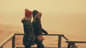 Två flickor tycker om regn i en vårskog nära havet 60 till 24fps 4K UHD lager videofilmer