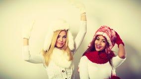Två flickor värme vinterkläder som har gyckel Fotografering för Bildbyråer