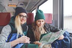 Två flickvänhandelsresande med ryggsäckar och inventariet som går på drevet och, håller ögonen på den ytterligare rutten på övers Royaltyfria Bilder