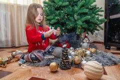 Två flickvänner är posera och bedra omkring julgranen royaltyfri foto