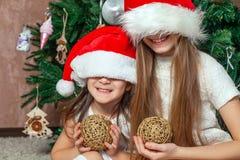 Två flickvänner är posera och bedra omkring julgranen royaltyfria bilder