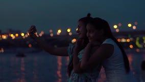 Två flickvänner gör selfie på en bakgrund av en nattstad långsam rörelse stock video