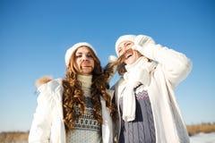 Två flickvänner har gyckel på vinterdagen Arkivfoton