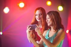 Två flickvänner i en nattklubb under strålkastaren royaltyfri foto