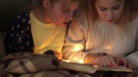 Två flickvänner läste en bok i säng i aftonen i ljuset av en liten elektrisk girland lager videofilmer