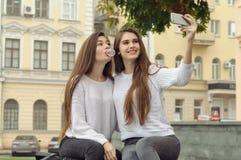 Två flickvänner pusta bubblor ut ur tuggummi, medan de gör Arkivfoton