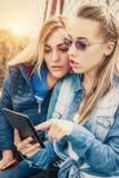 Två flickvänner som har gyckel med den digitala minnestavlan arkivfoto