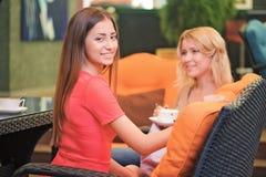 Två flickvänner som meddelar i kafé Royaltyfria Bilder