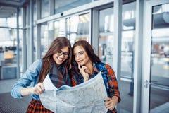 Två flickvänner som söker efter en ruttöversikt Konstbearbeta och retou Royaltyfria Foton