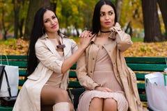 Två flickvänner som sitter på bänk med shopping Arkivfoton