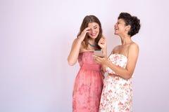 Två flickvänner som skrattar med en smartphone i hand Teknologi internet, kommunikation royaltyfria bilder