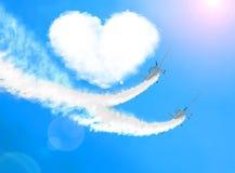 Två flygplan som en älska förälskad fluga för par runt om ett moln av hjärtor royaltyfria foton