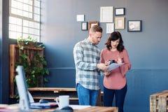 Två fokuserade arbetskollegor som tillsammans diskuterar skrivbordsarbete i ett kontor Royaltyfri Foto