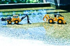 Två folk leksaker uppställda på vått cement visas i ljusa färger royaltyfri fotografi