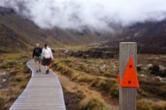 Två folk som fotvandrar Tongariro den alpina crossingen Royaltyfria Bilder