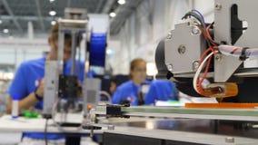 Två formgivare som arbetar i en designstudio, håller ögonen på en skrivare 3D En man gör en orientering för printing 3d En ung ma lager videofilmer