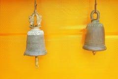 Två forntida mässingsklockor som hänger på guld- tygbakgrund på templet i Thailand arkivbilder