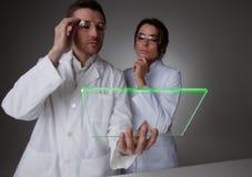 Två forskare med den futuristiska minnestavlan Arkivfoto