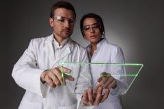 Två forskare med den futuristiska minnestavlan Arkivfoton