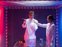 Två forskare som blandar kemikalieer i labb arkivfoton