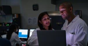 Två forskare som diskuterar över bärbara datorn 4k stock video