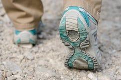 Två fot med att gå skor som fotvandrar på stenar Arkivfoton