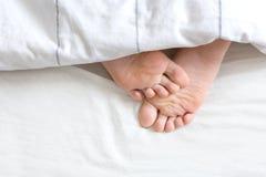 Två fot under sängkläderna Royaltyfria Foton