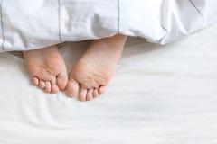 Två fot under sängkläderna Royaltyfri Foto