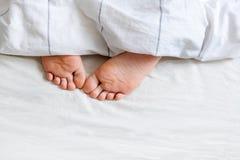 Två fot under sängkläderna Royaltyfri Bild