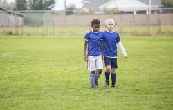 Två fotbolllagkamrater som går av fältet efter en förlust arkivbild