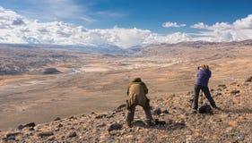 Två fotografer i berg En gråhårig man i ett kamouflageomslag och en rödhårig flicka i en randig tröja fotograferar Fotografering för Bildbyråer
