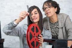 Två fotografkvinnor som ser filmen för rulle 16mm Fotografering för Bildbyråer