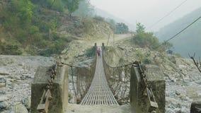 Två fotvandrare går vidare en inställd metallbro i Nepal stock video