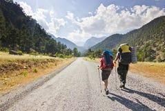 Två fotvandrare i kalkonberg som går på vägen med ryggsäckar fotografering för bildbyråer