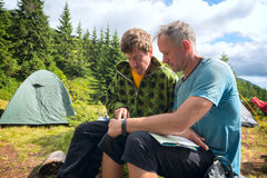 Två fotvandrare som diskuterar rutten som ser översikten Arkivbild
