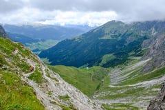 Två fotvandrare som stiger ned in i en dal i de Allgaeu moutainsna, Österrike Arkivbild