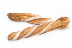 Två franska bröd i vit bakgrund Arkivfoto