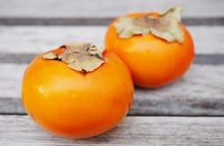 Två frukter för apelsinpersimonkaki Arkivfoto