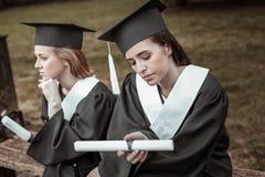 Två fundersamma kvinnlig som väntar på avläggande av examenpartiet arkivbild
