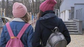 Två gå flickor, tonåringar i lock, lag, omslag med ryggsäckar, tillbaka sikt stock video
