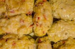 Två gånger bakade potatisar med smältt ost arkivfoto