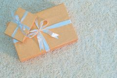 Två gåvaaskar av guld- färg som binds med band, ligger på en vit mjuk matta Förbereda sig för det nya året för ferie, jul, födels arkivfoton