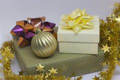 Två gåvaaskar och en guld- boll, pärlor på en ljus bakgrund arkivbild