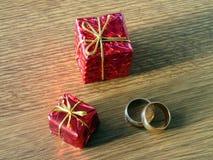 Två gåvor och guld- vigselringar Fotografering för Bildbyråer