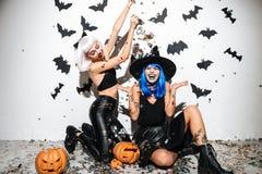 Två galna unga kvinnor i läder halloween kostymerar att posera Arkivbild