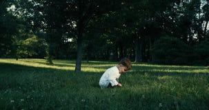 Två gamla år behandla som ett barn pojken som in spelar, parkerar Röd epos lager videofilmer
