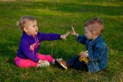 Två-gamla år pojke och flicka som plaing på exponeringsglaset i vår royaltyfria bilder