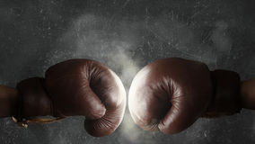 Två gamla bruna boxninghandskar som tillsammans slås Royaltyfria Bilder
